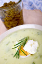 Green soup a fresh topped with a dollop of sour cream rosemary and an egg Royalty Free Stock Photo
