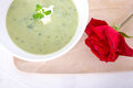Green soup vegetable in a white bowl and red rose flower Stock Photography