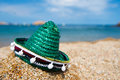 Green spanish straw hat at beach sombrero in sand the Royalty Free Stock Photography
