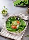 Green spinach pancakes or crepes with salmon and mashed avocado on a ceramic plate.