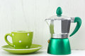 Green spotty mug and moka maker on white wooden background Royalty Free Stock Image