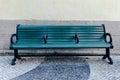 Green street bench on sidewalk Royalty Free Stock Photo