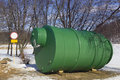 Green tank sewerage made fibreglass tank costs bank winter lake environmental pollution concept Royalty Free Stock Images