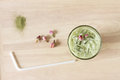 Green tea latte with dried rose on wooden background glass of decorated Royalty Free Stock Image