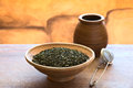 Green tea leaves dried in bowl with a strainer and wooden cup photographed with natural light selective focus focus one Royalty Free Stock Photography