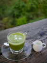 Green tea with milk jug glass cup of on wooden table outdoors next to Royalty Free Stock Photo