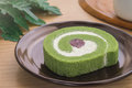 Green tea roll cake with red bean on plate