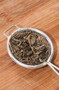 Green tea in tea strainer on the wooden board Royalty Free Stock Photo