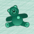 Green teddy bear with four leaf clover and fabric swatch behind Stock Photography