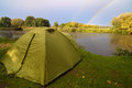 Green tent pitched on the bank of a lake. Royalty Free Stock Photo