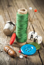 Green thread sewing spool single of and scattered buttons and needles Stock Photos