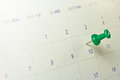 Green thumb tack on calendar Stock Image