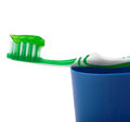 Green toothbrush with paste lying on blue plastic cup isolated over white background Royalty Free Stock Photo