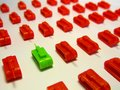 Green toy tank opposite to rows of red toy tanks to symbolize Brexit and political clash. Royalty Free Stock Photo