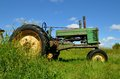 Green tractor in long grass an old is parked a pasture with Stock Images