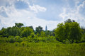 Green trees and a church in the distance. Royalty Free Stock Photo