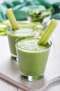Green vegetable smoothie with celery and spinach on wooden background Stock Images