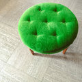 Green velvet stool on tiled floor Royalty Free Stock Photo