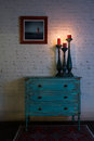 Green vintage cabinet, candlesticks and hanged painting on bricks wall Royalty Free Stock Photo
