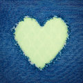 Green vintage heart on blue denim fabric shape for copy space torn from jeans romantic love concept background Royalty Free Stock Photo