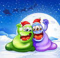 A green and a violet monster wearing a red hat for christmas Royalty Free Stock Photo