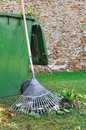 Green waste rake for collect leaves near a bin for plant Stock Image
