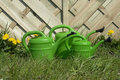Green watering cans on lawn Royalty Free Stock Photos