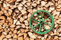 Green wheel old wooden carriage on the heap of firewood background Stock Photography