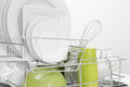 Green and white dishes drying on dish rack Royalty Free Stock Photo
