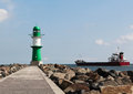 Green and white lighthouse and cargo ship leaving port Royalty Free Stock Photo