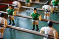 Green and white table football with steel shafts crafted players focus on individual player in strip Stock Image