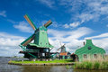 Green windmill at dutch zaanse schans the near the river Stock Image