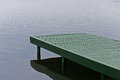 Green wooden pontoon on blue water Stock Photos