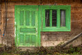 Green wooden window with green door in an abandoned house Royalty Free Stock Photo