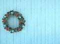 Green wreath with blue and red bow on antique teal aqua rustic wood Royalty Free Stock Photo