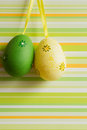 Green and yellow hanged Easter eggs on striped background Royalty Free Stock Photo