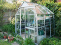 Greenhouse typical domestic aluminium in british garden Royalty Free Stock Photo
