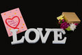 Greeting card, gift box and alphabet love on black background Royalty Free Stock Photo