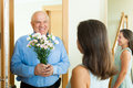 Greeting of loving mature couple with flowers at home door Royalty Free Stock Images