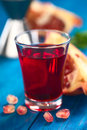 Grenadine syrup in shot glass with pomegranate seeds in the front and pomegranate in the back selective focus focus on the front Royalty Free Stock Photos