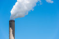 Grey chimney with white smoke closeup of a bright blue sky polluting from a high Stock Images