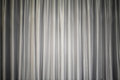 Light gray fabric curtain closed like on a theater show stage, with light in the middle, background, texture Royalty Free Stock Photo