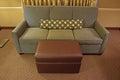 Grey fabric sofa con l ottomano del cuoio di brown ed il cuscino stretto lungo Fotografie Stock