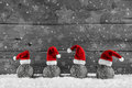 Grey festive wooden christmas background with four santa hats on Royalty Free Stock Photo