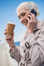 Grey haired woman talking on smartphone outdoors