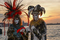 Grey masked couple at venice carnival sunset Royalty Free Stock Images