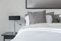 Grey pillow on white bed in modern bedroom with black lamp Royalty Free Stock Photo