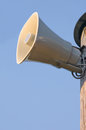 Grey plastic horn loudspeaker on pole post, blue sky, large detailed vertical closeup Royalty Free Stock Photo