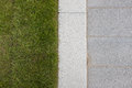 Grey stone paving & kerb adjacent to green grass lawn Royalty Free Stock Photo