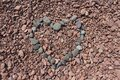 Heart Shaped Grey Rocks over Rose Colored Stones Royalty Free Stock Photo